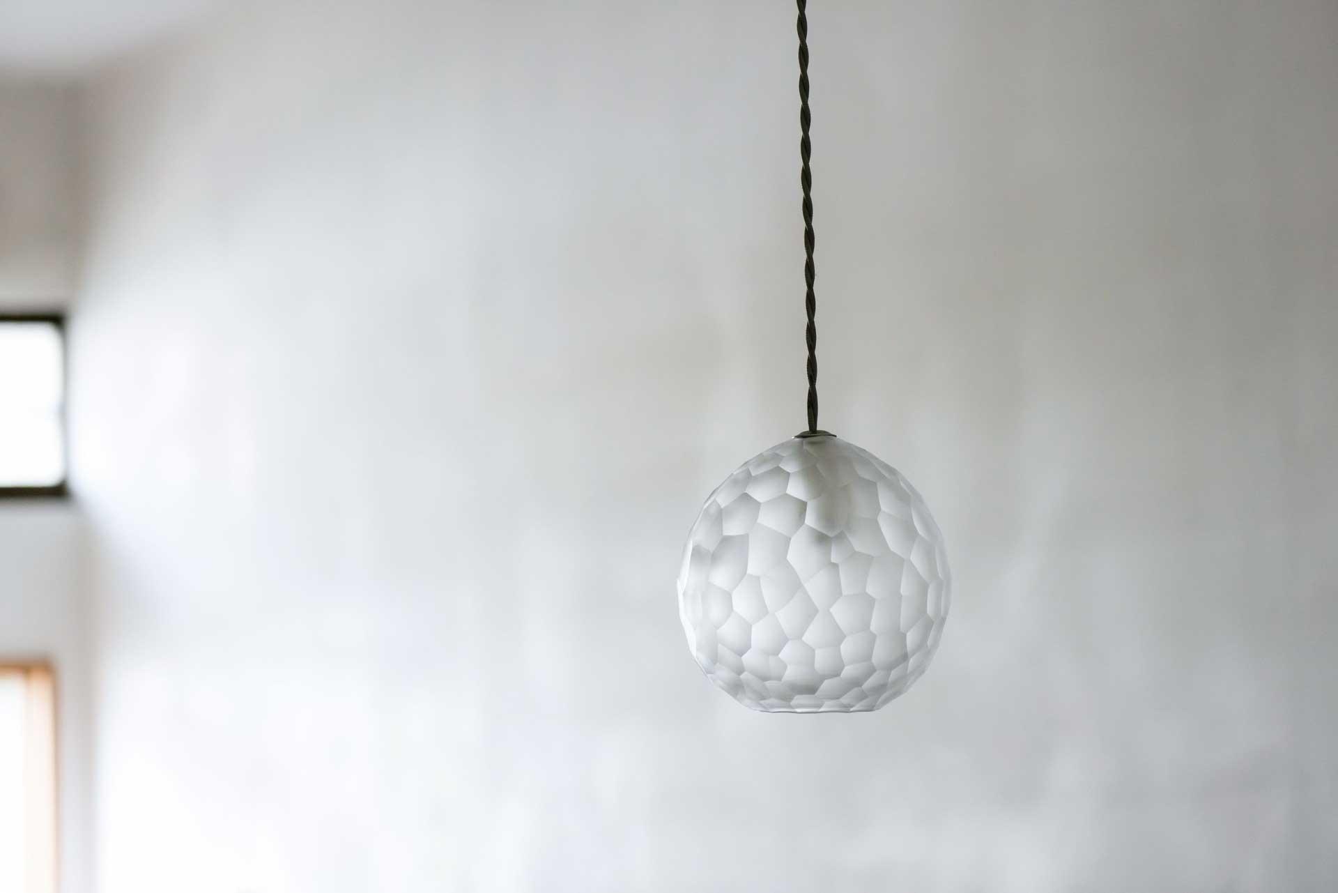 ギャラリーの天井から吊るした削紋ランプシェード。白い塗り壁を背景にしたすっきり美しい写真
